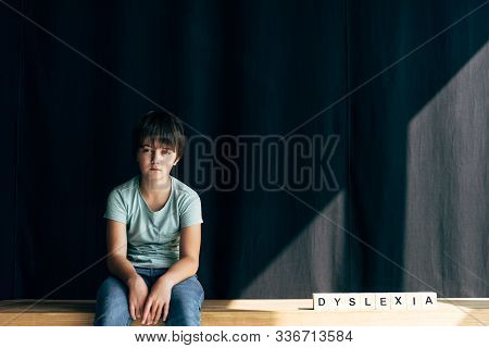 Kid With Dyslexia Looking At Camera And Sitting Near Wooden Cubes With Lettering Dyslexia