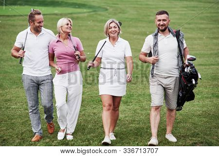 Walking The Lawn. Cheerful Friends Spending Time In The Golf Field With Sticks And Good Mood.