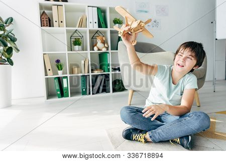 Cute Kid With Dyslexia Sitting On Floor And Playing With Wooden Plane
