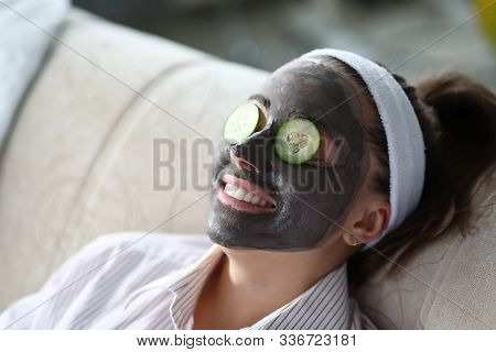 Woman Makes Gray Clay Facial Mask At Home. Put Cut Cucumber On Her Eyes Like Glasses. Spa Home Beait