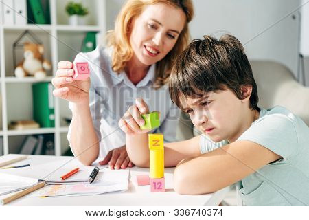 Kid With Dyslexia And Smiling Child Psychologist Playing With Building Blocks