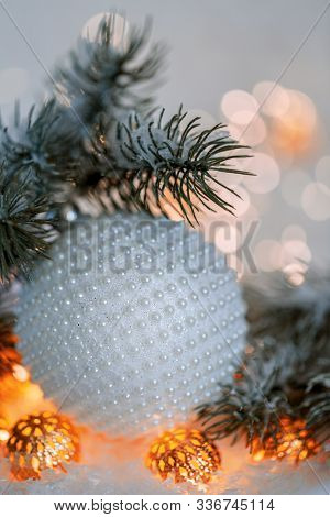 Christmas And New Year Holiday Greeting Card. White Ball With Nacre Pearls, Pine Branches And A Garl