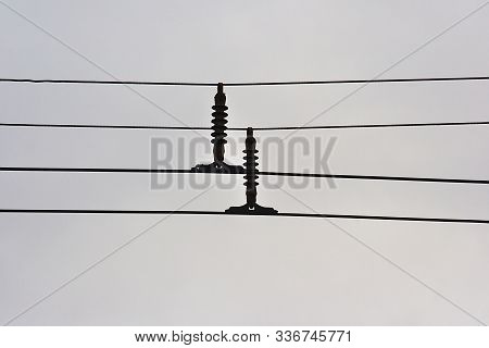 trolley wires with dielectric insulators on the background of the autumn sky poster