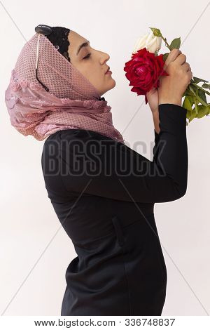 Stylish Muslim Woman In Traditional Islamic Clothing Holding Flower Bouquet. Portrait Of Beautiful M