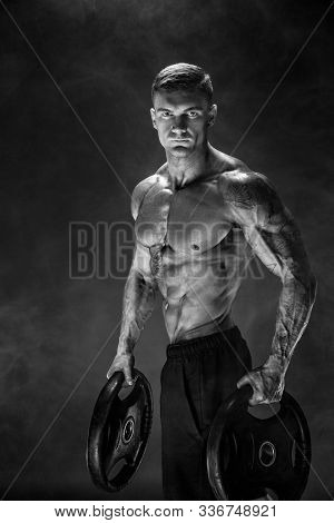 Very Brawny Guy Bodybuilder. Bodybuilder With Dumbbells In His Arms On Dark Background With Smoke.