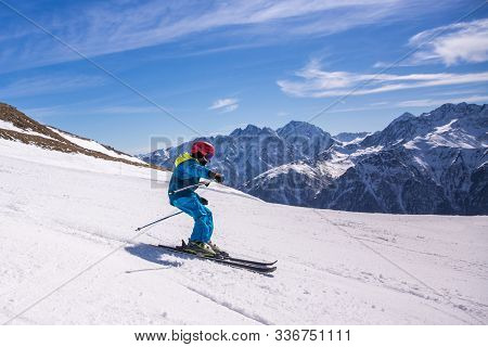 Little Boy In Blue And Yellow Ski Costume Skiing In Downhill Slope. Winter Sport Recreational Activi