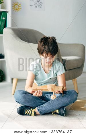 Sad Kid With Dyslexia Sitting On Floor And Holding Wooden Plane