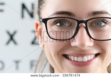 Focus On Beautiful Woman Wearing Glasses In Black Stylish Frame. Cheerful Ophthalmologist Looking At