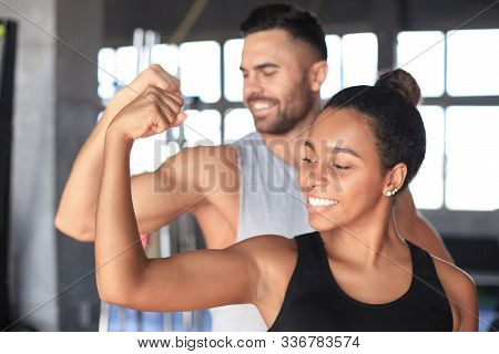 Cheerful Sportive Couple Training Together And Showing Biceps At The Gym.