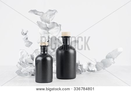 Blank Cosmetic Glass Black Bottles With Beige Bungs Decorated Silver Leaves On Light White Wood Tabl
