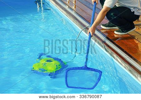 Pool Cleaner During His Work. Cleaning Robot For Cleaning The Botton Of Swimming Pools. Hotel Staff