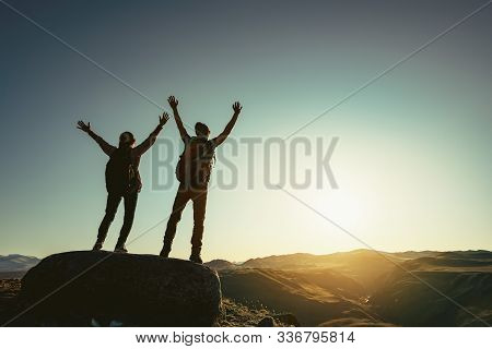 Two Happy Hikers Stands With Raised Arms Against Sunset And Enjoys Mountains View
