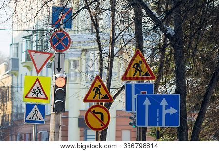 A Large Number Of Road Signs, Symbols Of Detours, Road Repairs Near The Traffic Light With A Pedestr