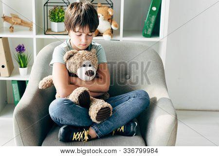 Kid With Dyslexia Holding Teddy Bear And Sitting On Armchair