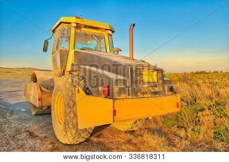 Work In Progress, Industrial Machine. Perspective View Of Yellow Steamroller In A Suggestive Constru