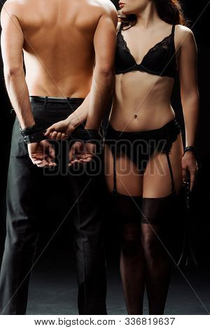 Cropped View Of Dominant Woman In Underwear Standing Near Muscular Man In Handcuffs On Black
