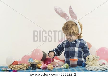 Funny Little Boy With Bunny Ears And Colorful Easter Eggs. Easter Holiday. Colouring Eggs For Easter