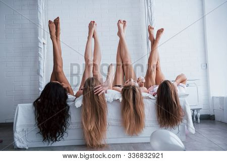 Four Young Women With Good Body Shape Lying On The Bed With Their Legs Up.