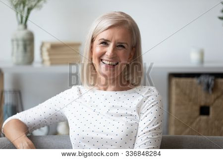 Headshot Aged Woman Smiling Sitting On Couch Looking At Camera