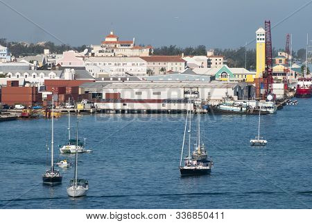 The View Of Yachts Drifting In Nassau Harbour And Nassau Downtown With An Airplane Flying Over In A