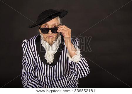 Old Grandma In A White-black Striped Jacket