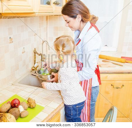 Little Girl And Mother Cooking Together In The Kitchen.