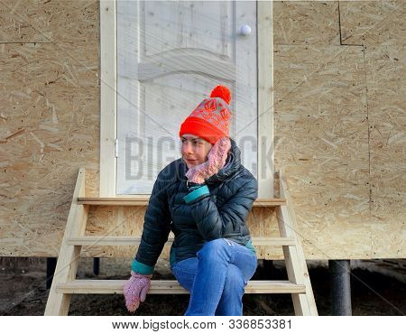 Young Female In Winter Clothes Sittin On A Porch Of Just Built Woodchip House, Particular Focus Outd