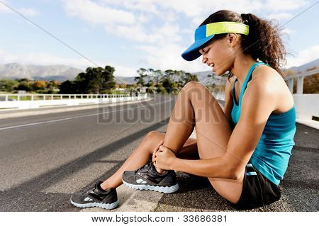 Runner with ankle injury has sprained and strained ankle, painful expression. typical road running problem associated with shoe choice