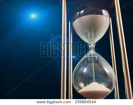 Hourglass On A Stand, Black Background. Glass Hourglass In The Case. Glass Time Meter. Concept: Time
