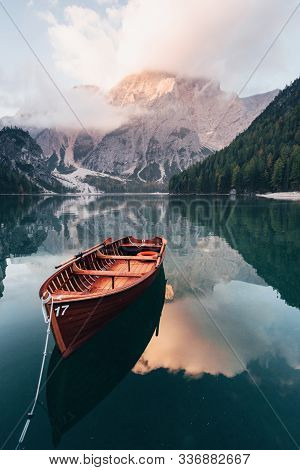 Vertical Photo. Wooden Boat On The Crystal Lake With Majestic Mountain Behind. Reflection In The Wat
