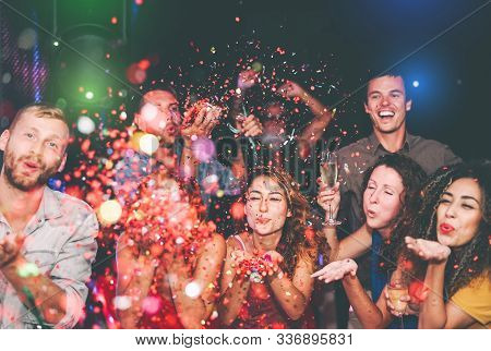 Happy Friends Doing Party Throwing Confetti In Nightclub - Group Young People Having Fun Celebrating