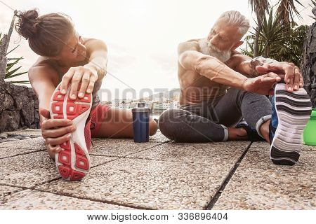 Fitness Couple Doing Stretching Exercise Outdoor - Happy Athletes Making Workout Session At Sunset O