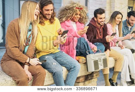 Group happy friends using mobile smartphones in the city - Millennial young people having fun with new trendy apps for social media networks - Tech generation z and youth lifestyle culture concept