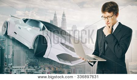 Businessman Holding Laptop With Sportscar And Modern Skyscraper On Background
