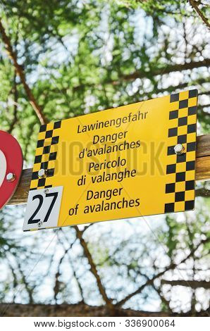 Yellow Tourist Sign Warns Of Avalanches In Four Different Languages. Warning In German, French, Ital