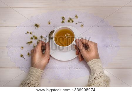 Tea With Camomile. Girl Holds A Cup With Tea On A White Wooden Background, Top View. For Immunity, F