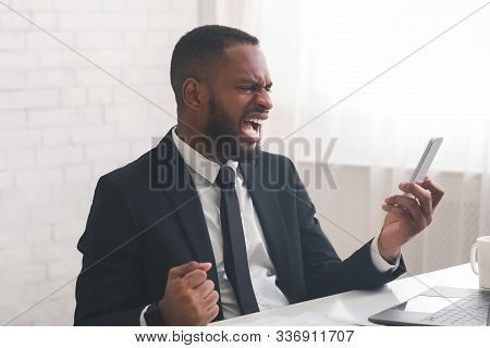 Enraged African American General Manager Reading On Phone Emails From Displeased Clients, Angry With
