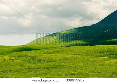 Soft Hills With Green Grass Under Cloudy Sky