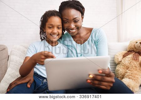 Happy African Family Making Video Call To Grandparents Using Tablet At Home. Copy Space