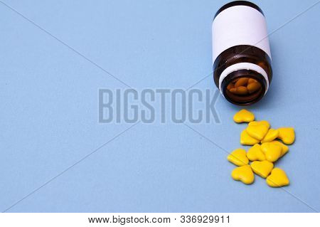 Jar With Pills In The Shape Of A Heart Sprinkled On A Blue Background. I Love The Treatment. Medicat