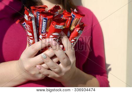 Kharkov, Ukraine - October 21, 2019: A Young Caucasian Brunette Girl Holds Many Kit Kat Chocolate Ba