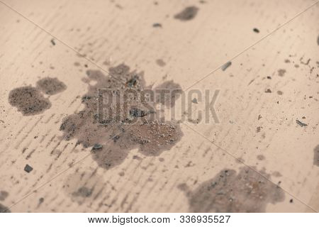 Oil stains on cardboard. Cheap oil leak absorbing.