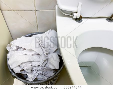 Overflowing Trash Can, Dustbin Full Of Used Toilet Paper Near The Toilet Bowl In A Public Restroom.