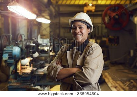 Waist Up Portrait Of Mixed-race Female Worker Posing Confidently While Standing With Arms Crossed In