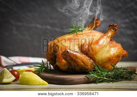 Whole Roasted Chicken Rosemary And Tomato Lemon On Wooden Cutting Board / Baked Chicken Grilled Barb
