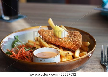 Fried Fish Fellet Wiht French Fries And Veggies On Plate In Restuarant