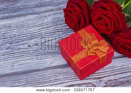 Red Roses And Jewelry Gift Box. Red Jewelry Present Box And Blooming Roses On Gray Wooden Background