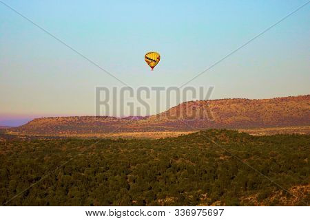 October 16, 2019 In Sedona, Az:  Hot Air Balloon Riding Over A Forest On A Mountain Plateau Overlook