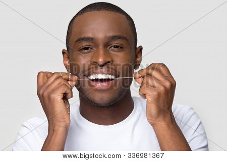 Happy African American Man With Healthy Smile Using Dental Floss