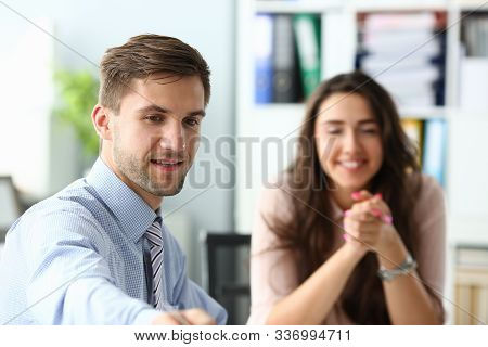 Portrait Of Business People Meeting In Office. Man Sitting At Table And Signing Documents. Cheerful